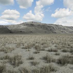 Some flat desert between mountains.